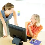 Two Young Women in Front of the Computer Talking